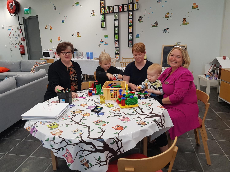 Tre kvinnor och två barn sitter runt ett bort med leksaker.