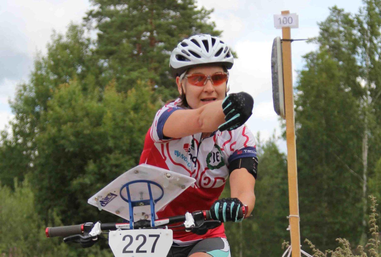 Sportigt klädd kvinna cyklar i terräng