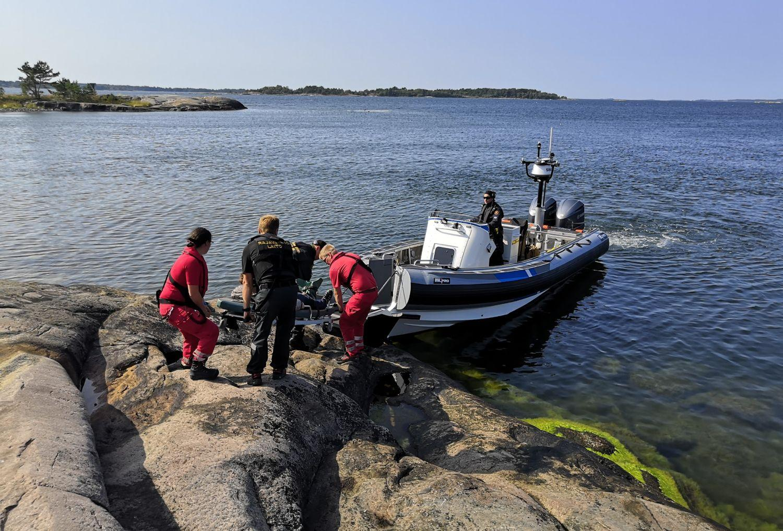 Räddningspersonal hjälper patient ombord på en en motorbåt.