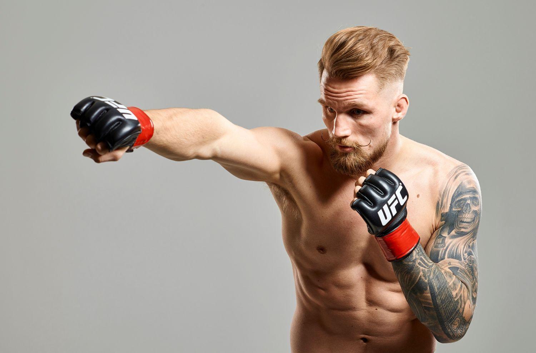 Kampsportare med boxningshandskar poserar utan skjorta