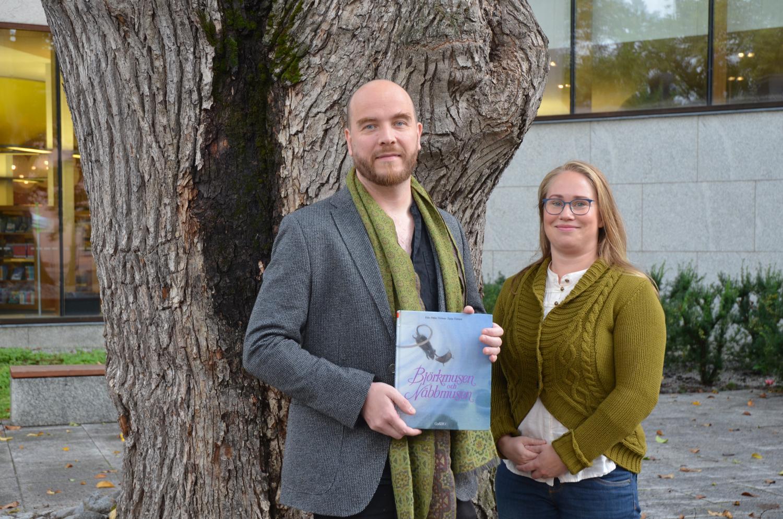 """En manlig regissör och en kvinnlig skådespelare med barnboken """"Björkmusen och näbbmusen"""" i handen"""