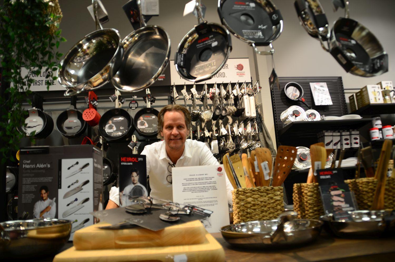 Leende man i butik fylld med köksredskap