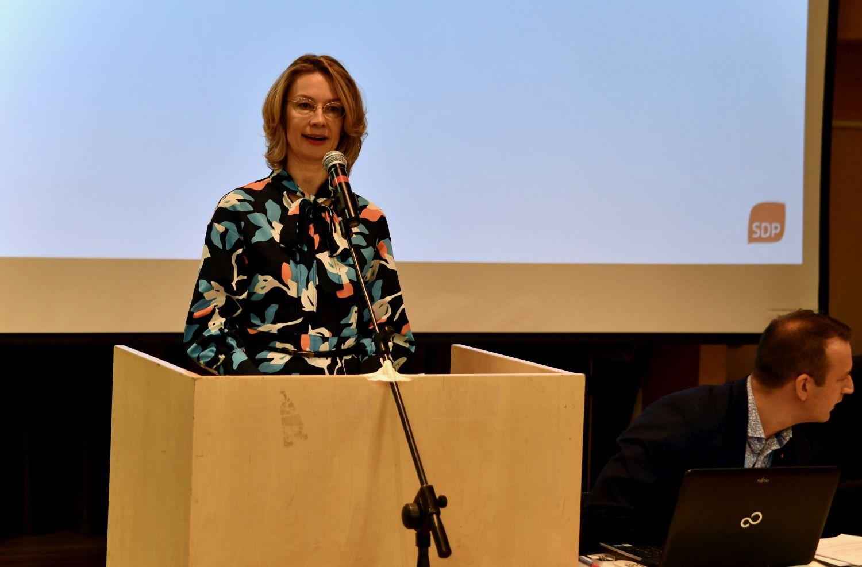 Kvinna som står i en talarstol och talar