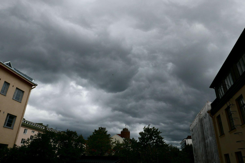Mörka moln ovanför hustak.