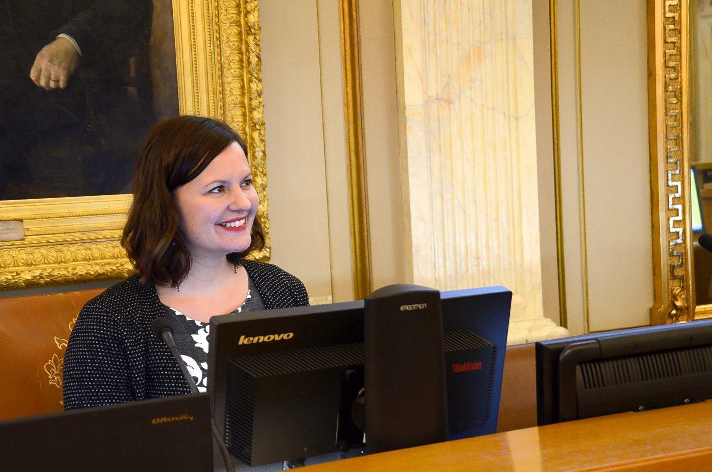 Leende kvinna med en dator framför sig.