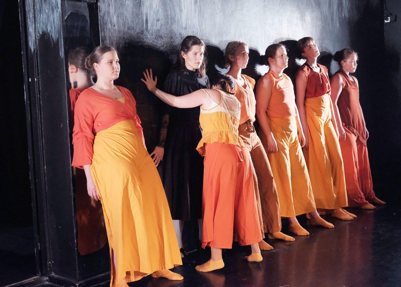 Orangeklädda skådespelare på rad på en scen.