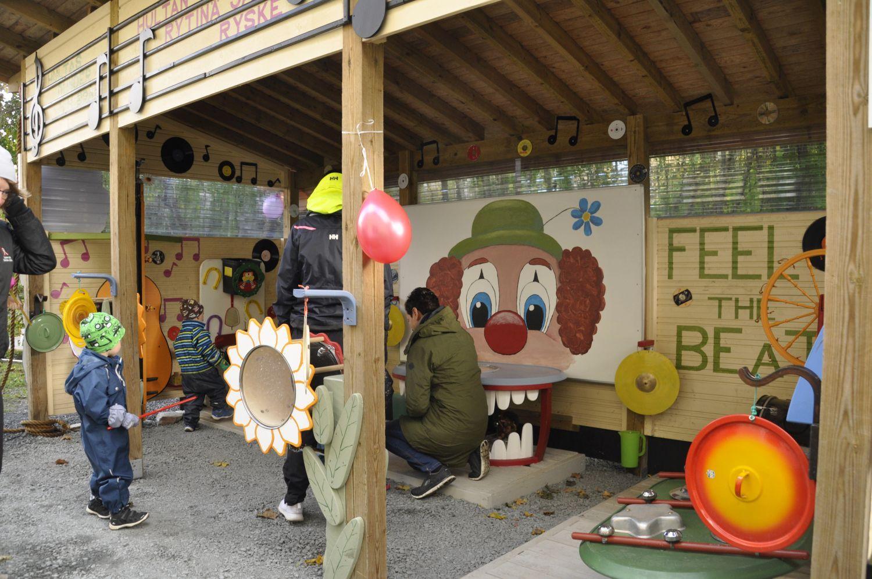 En liten byggnad full av instrument (typ kastrullock), färggranna målningar och roliga former.