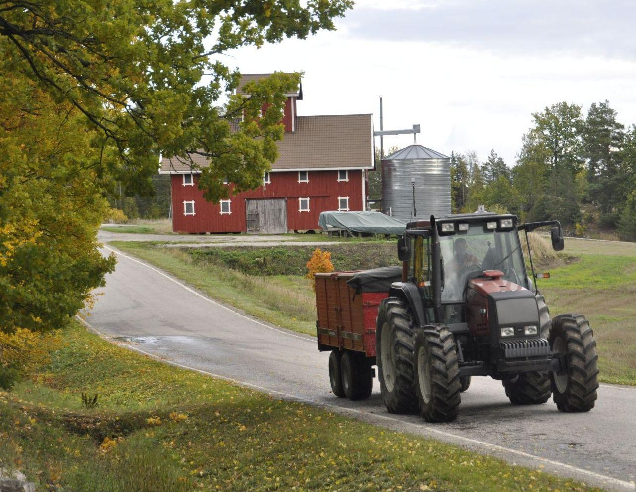 Traktor med släp kommer körande på vägen. I bakgrunden syns en tork.