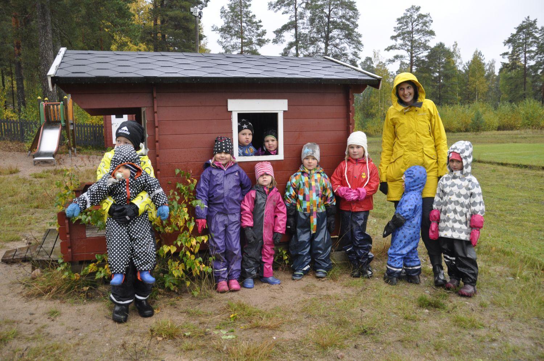 Ett gäng med 10 barn står vid en lekstuga i regnet tillsamman med en vuxen