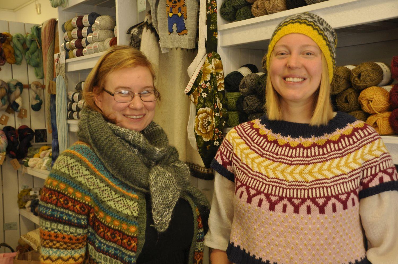 Två glada damer i stickade kläder framför hyllor med garn