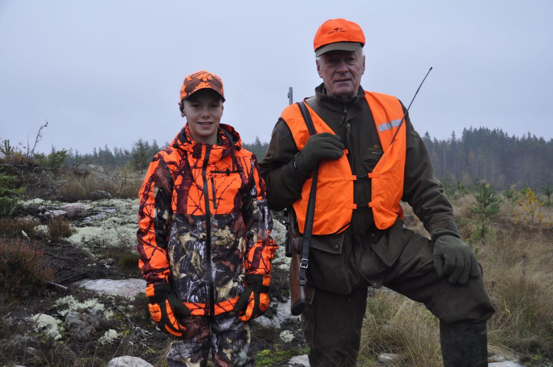 Ett barn och en äldre man i jaktkläder
