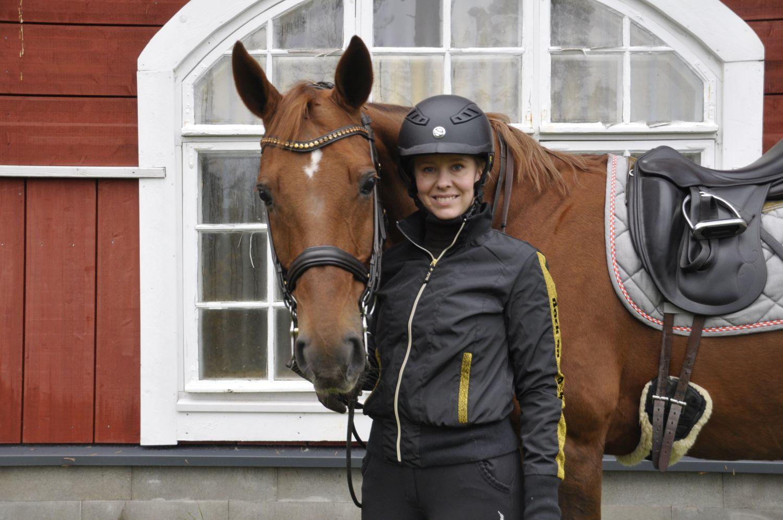 Häst och en ryttare som står på marken. Fotot taget utanför manegen i Björkboda.