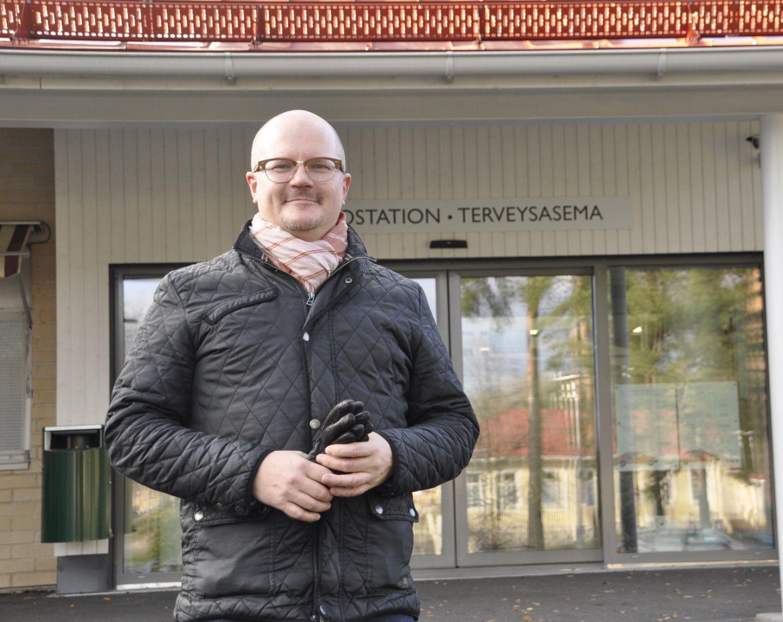 En man står utanför ingången till en hälsostation