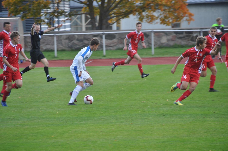 Finlands spelare i vit skjorta med bollen mot många motståndare i röd skjorta på Pajbackas gräsplan.