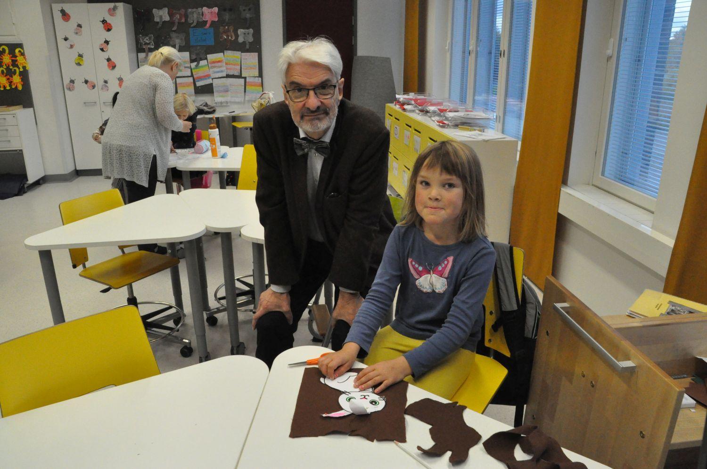 En äldre man och en liten flicka i en skolklass.