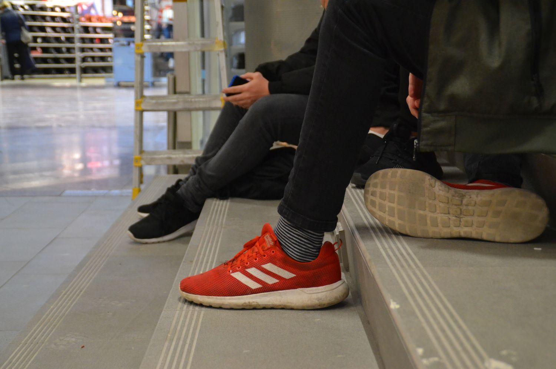 Fötterna på några killar som sitter på en trappa.