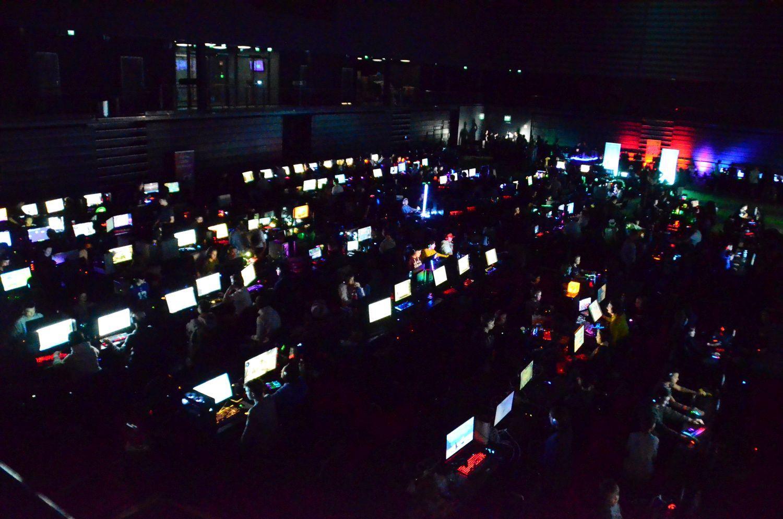 Mång alysande datorskärmar i en mörk sal.