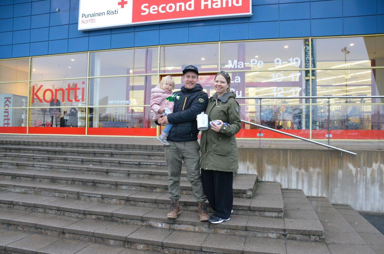 Ett barn, en man och en kvinna på trapporna till en affär.