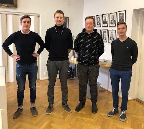 Fyra unga män står på rad