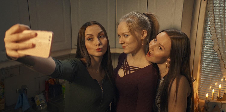 Tre flickor fotar sig själva med en mobiltelefon.