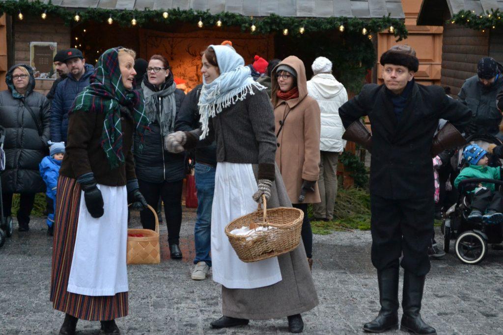 Tre personer i gammaldags kläder på torget