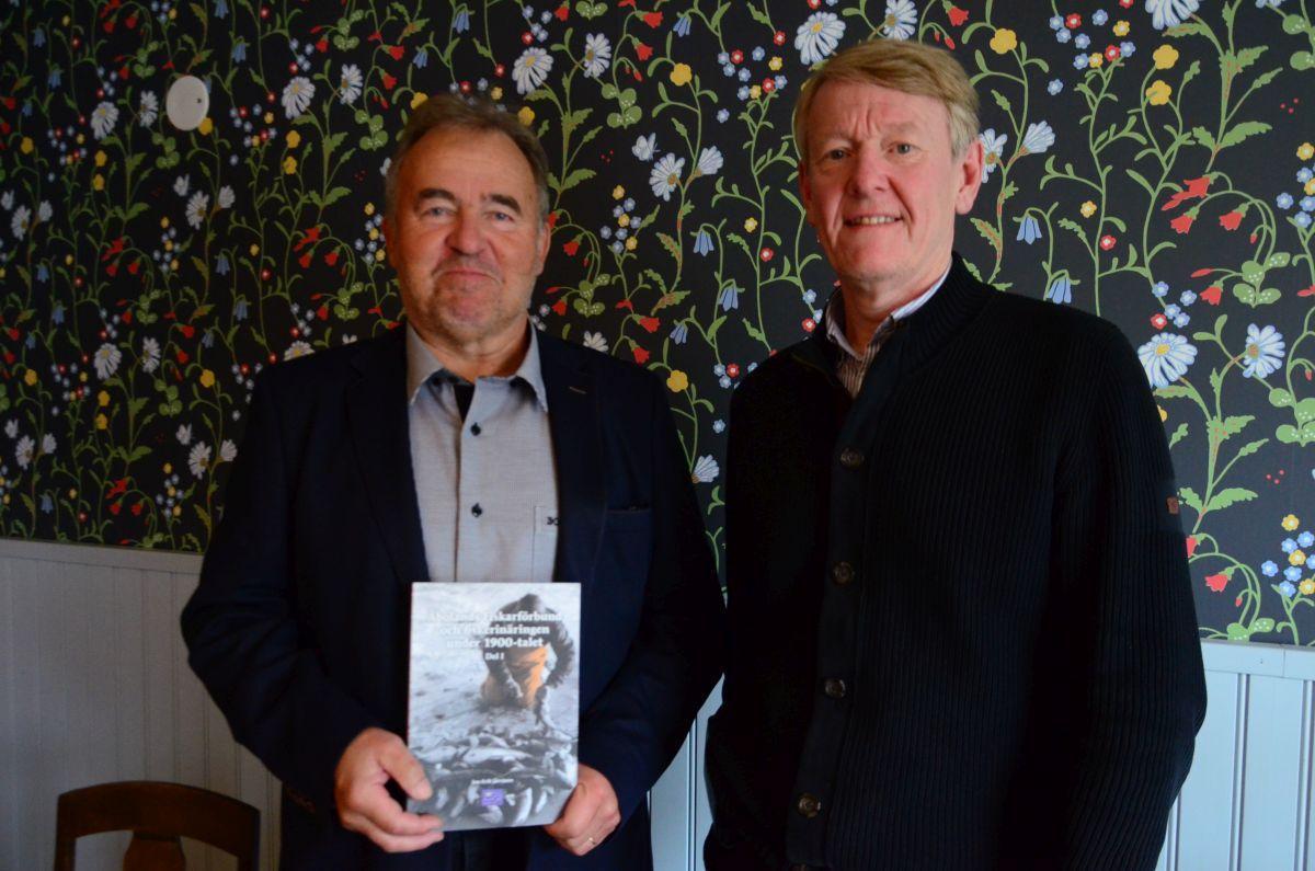 två män står mot en blommig vägg, den ena håller boken om fiskarförbundet i handen