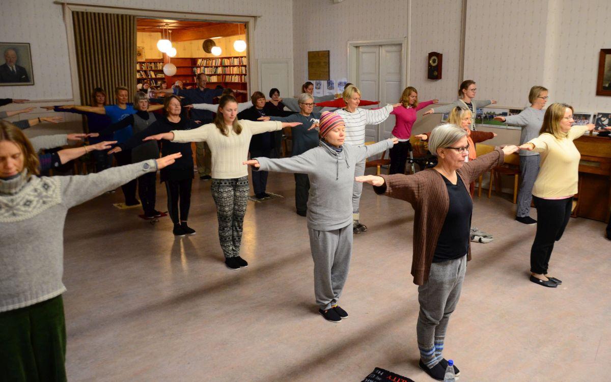 många mogna människor i en sal står stilla med armarna utåtsträckta