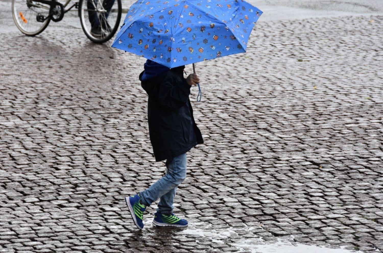 Barn med paraply går på kullerstensgata