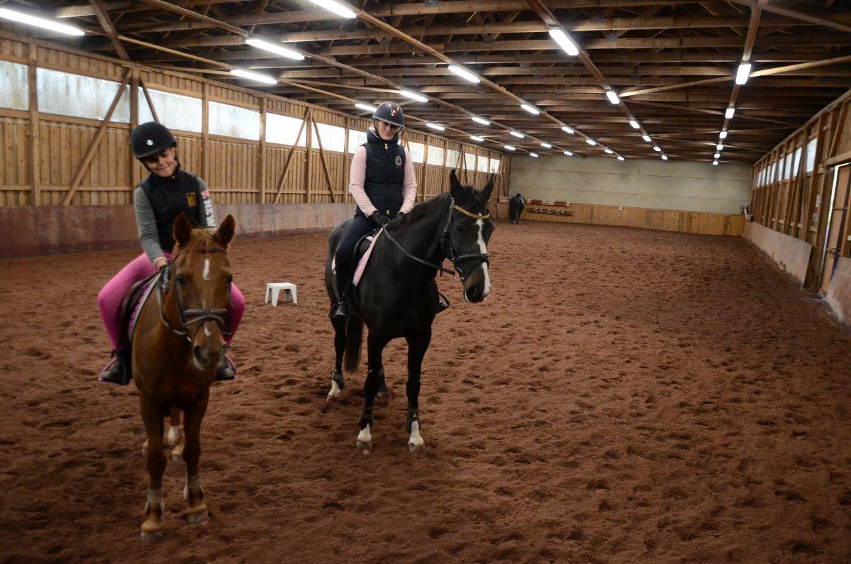 två flickor sitter i sadeln på ponny respektive häst