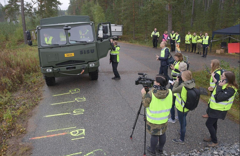 Militärlastbil omgiven av människor