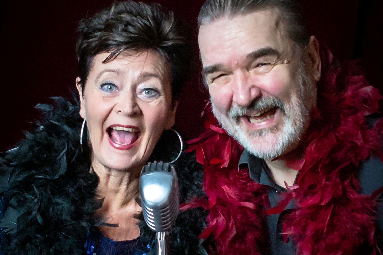Festligt klädd kvinna och man med mikrofon