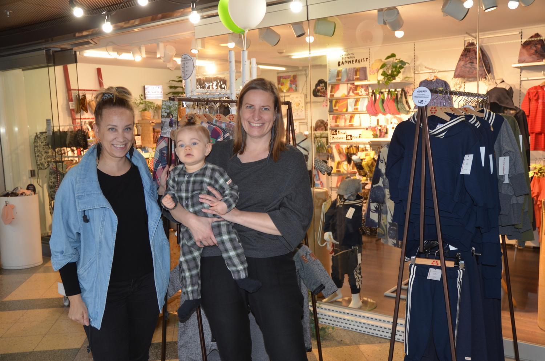 Två kvinnor och ett litet barn i en klädaffär där kläderna tillverkas av återvunna textilier.