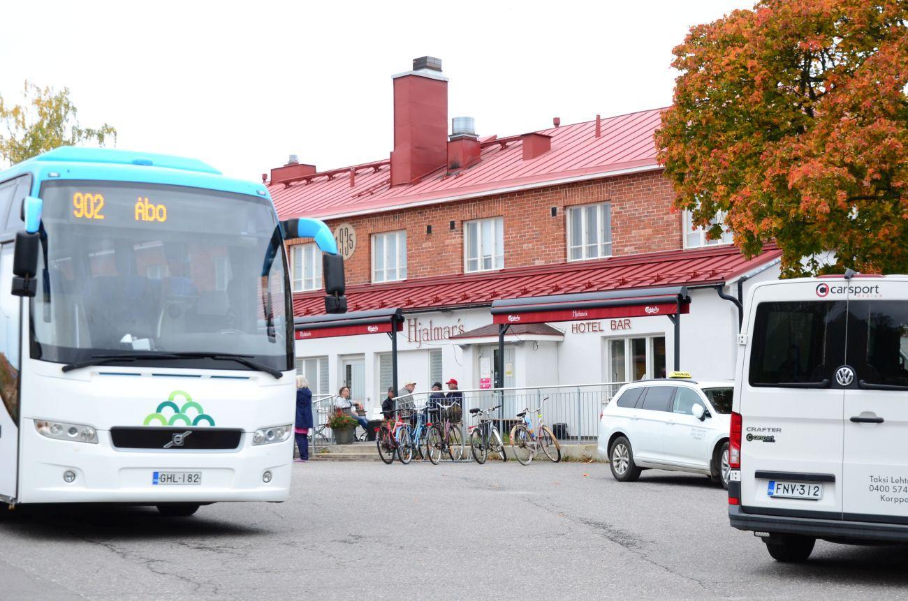 vitt hus med rött tak, litter i Korpo centrum. Framför står en buss på väg till Åbo