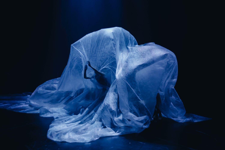 Dansare under ett stort plastskynke.