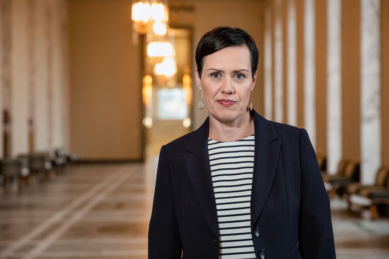 Kvinna i kavaj och randig skjorta i Riksdagens korridor.