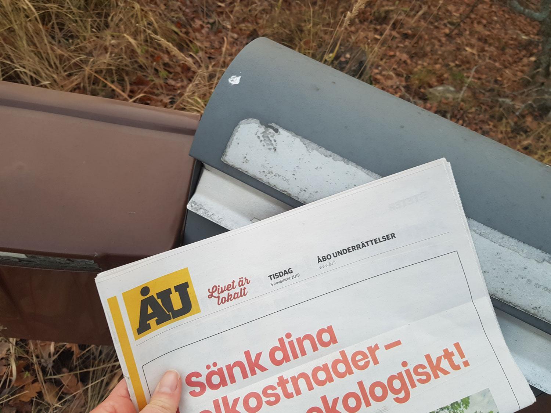 En hand håller en ÅU-tidning vid två postlådor