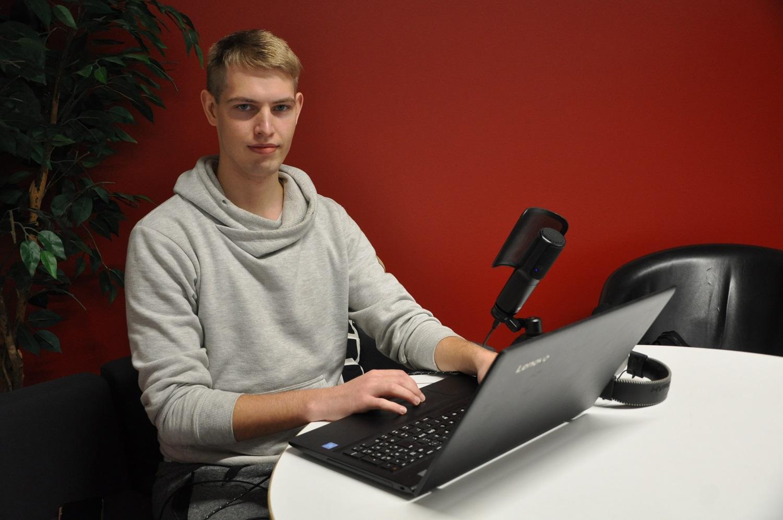 Ung man sitter framför dator.