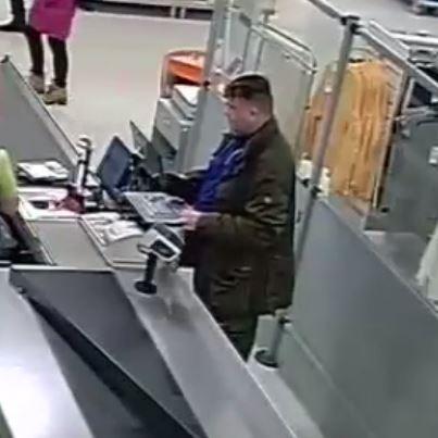 En man står vid en matbutikskassa fotad med övervakningskamera