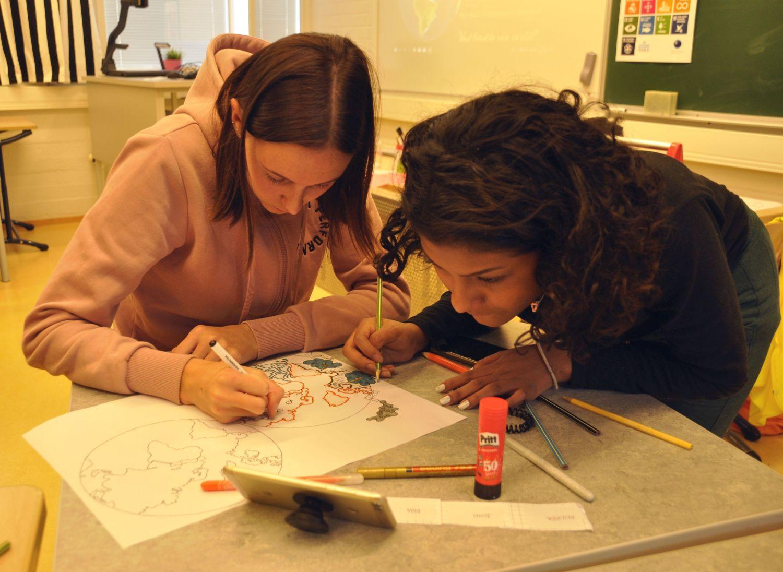 två elever lutade över ett bord, fullt koncentrerade på den affisch de ritar