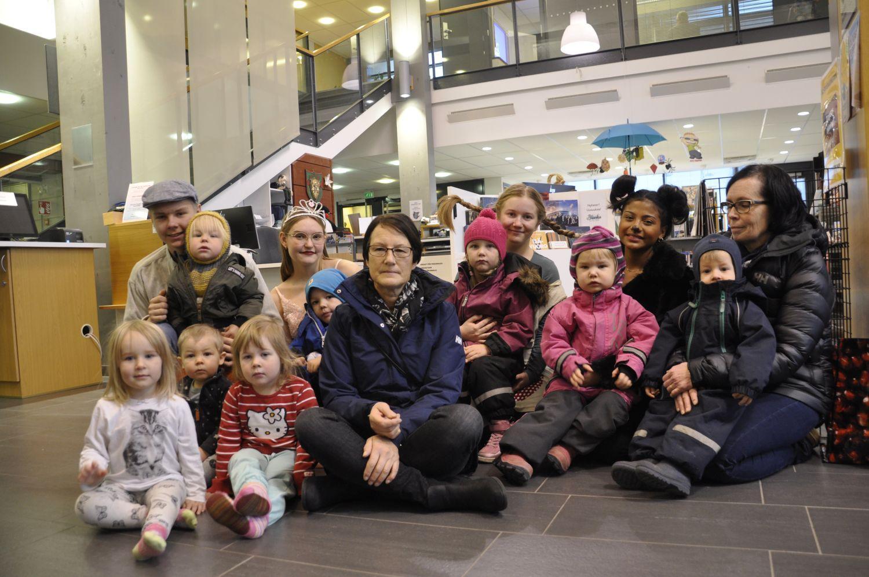 Vuxna, unga och barn sitter på golvet arrangerade till en gruppbild