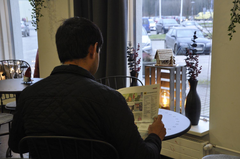 Man sitter vid ett cafébord och läser tidningen. Ett fönster med ett ljus synd framför mannen, som är fotad bakifrån.