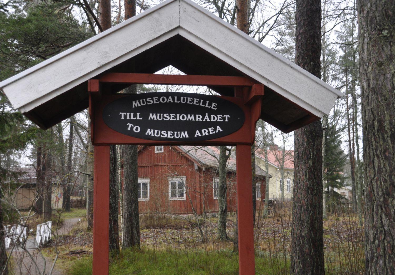En museiområdesskylt med ett litet tak. Genom skylten syns en röd byggnad och längre bort en gul.