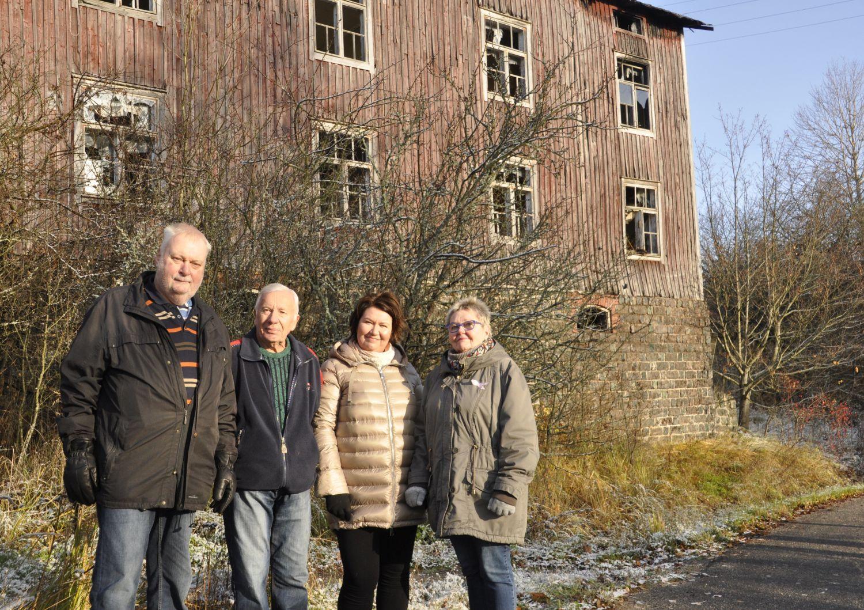 Fyra personer framför att förfallet hus