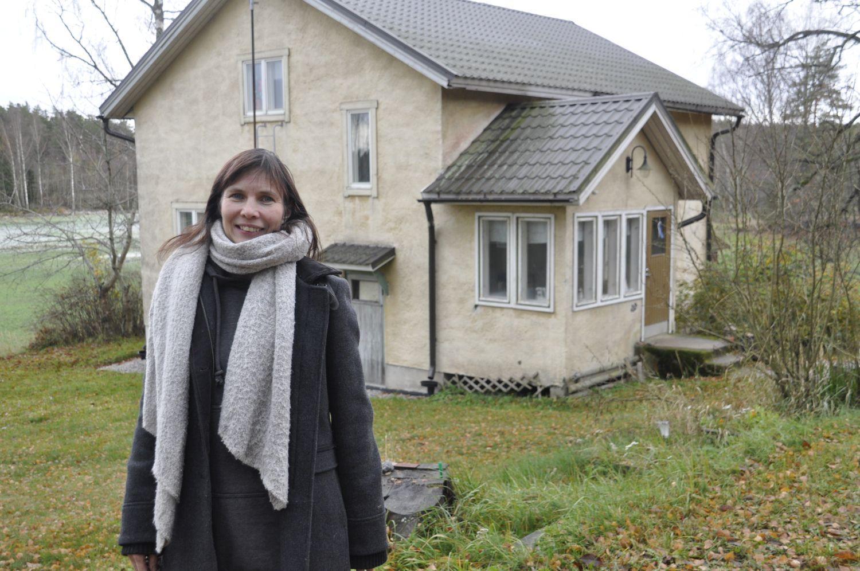 Person framför ett gult egnahemshus