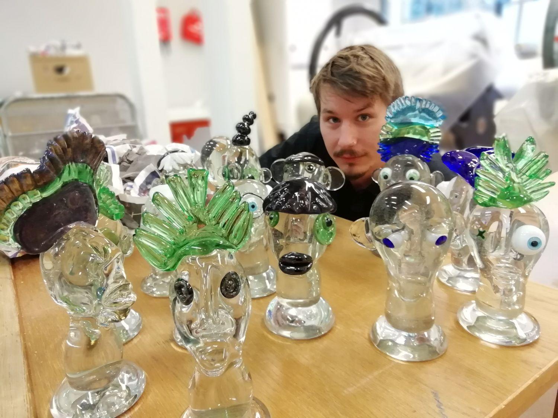Glasskulpturer på ett bard. Bakom dem skymtar konstnären