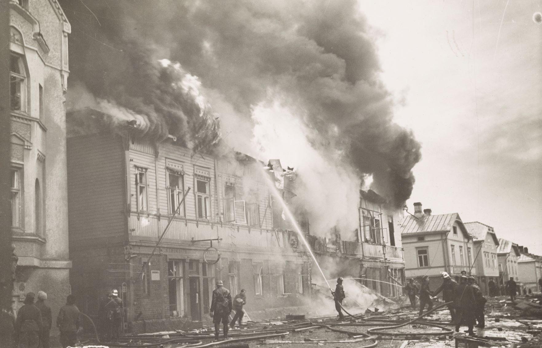 Ett svartvitt foto föreställandes ett trähus som brinner och brandkåren som försöker släcka