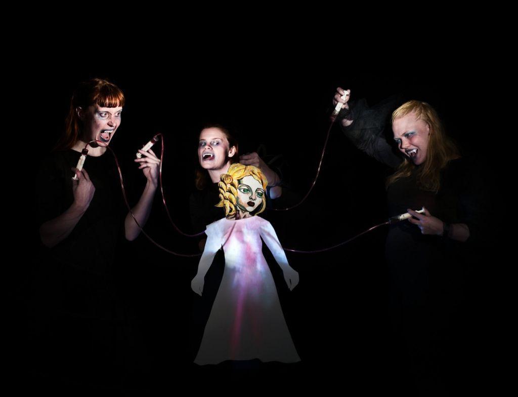 Tre svartklädda personer med huggtänder styr en pappersdocka i prinsessklänning.