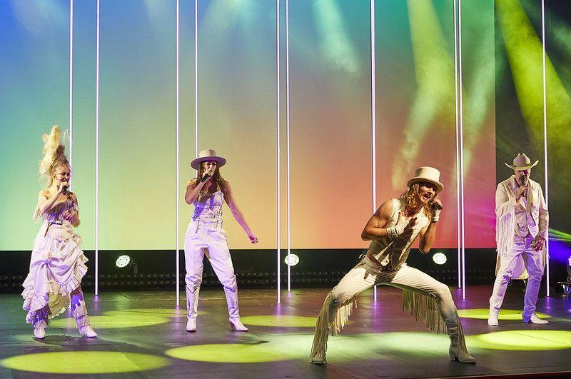 fyra människor i vita glitterkläder på scen, uppträder med sång