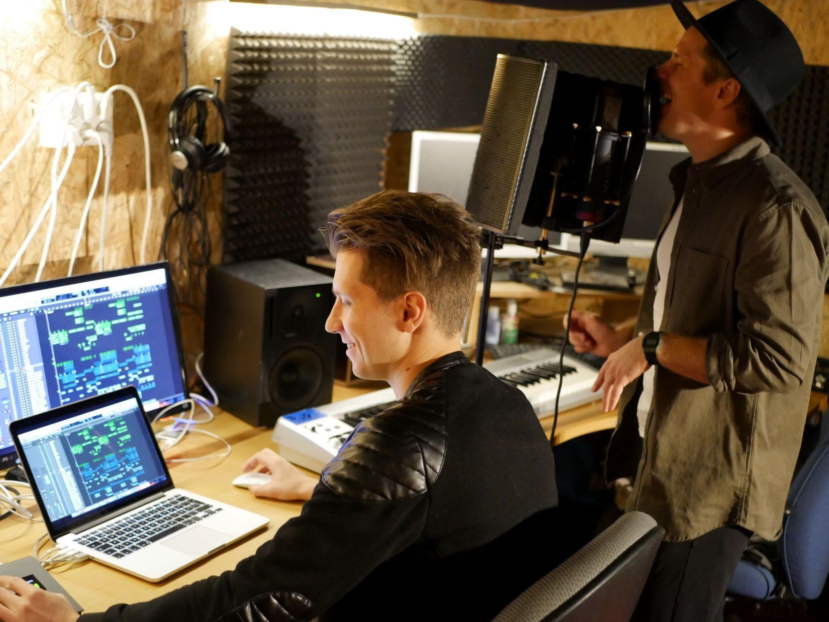 En person sitter vid datorn och den andra står och sjunger in i en mukrofon