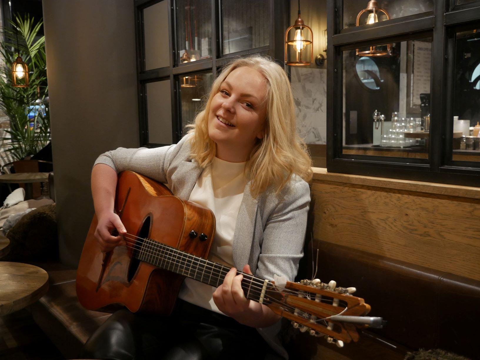 En kvinna sitter på café och spelar gitarr